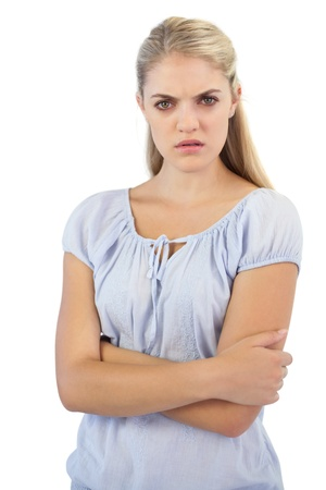 exasperated: Outraged blonde woman  with arms crossed on white background