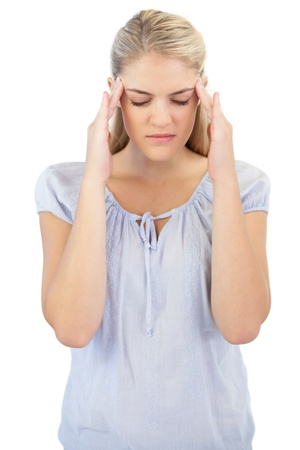 Unsmiling blonde woman has headache on white background photo