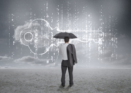 Businessman with an umbrella looking at a big key with grey sky on the background photo