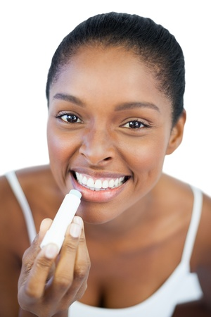 Woman putting lip balm on her lips on white background Stock Photo