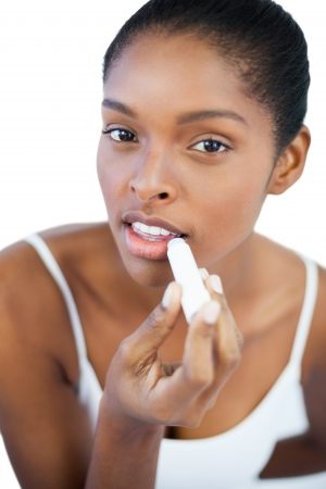Pretty woman putting lip balm on her lips on white background