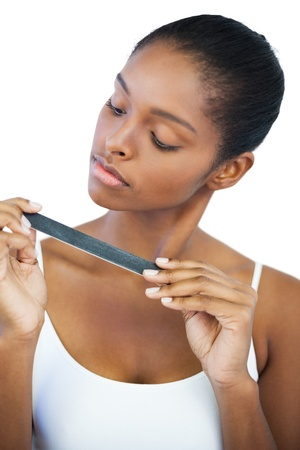 Serious woman looking at her nail file on white background photo
