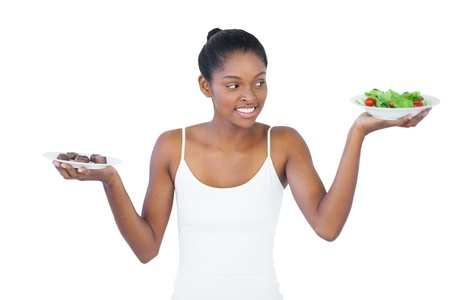 healthily: Cheerful woman deciding to eat healthily or not on white background Stock Photo