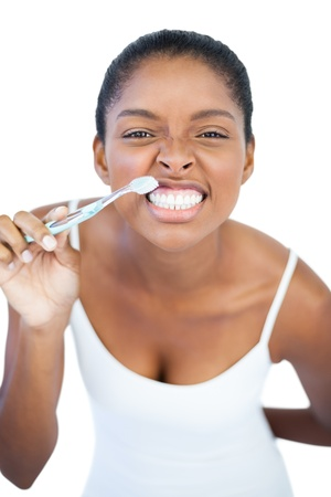 Woman brushing her teeth on white background photo