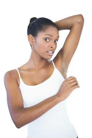 Woman putting deodorant on her armpit on white background photo