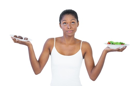 healthily: Conflicted woman deciding to eat healthily or not on white background