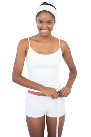 girth: Woman measuring her waist on white background
