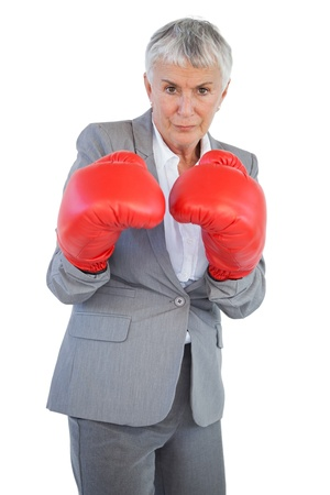 Serious businesswoman standing with her boxing gloves on white background photo