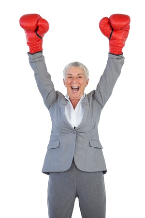 Happy businesswoman wearing boxing gloves and raising her arms on white blackground photo