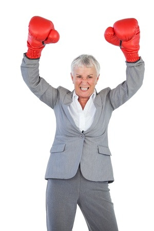 Businesswoman wearing boxing gloves and raising her arms on white background photo