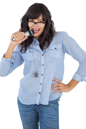 Young woman with her hand on hip singing on white background photo
