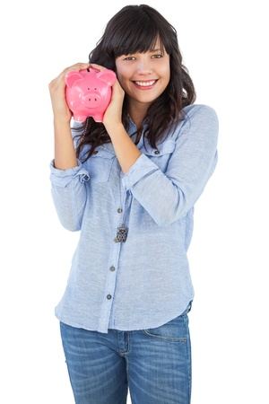 Smiling young woman shaking her piggy bank on white background photo