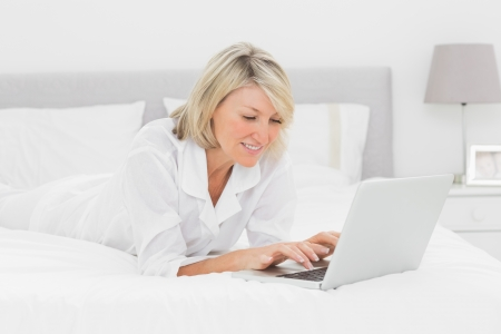 Smiling woman using her laptop on her bed at home in bedroom