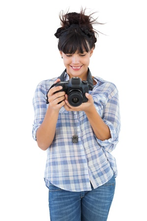 Smiling young woman holding camera for taking picture on white background photo