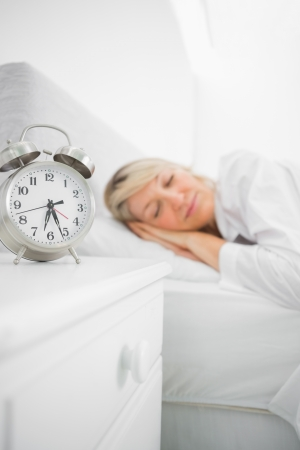 Blonde woman asleep in bed before her alarm clock goes off Stock Photo - 20625824