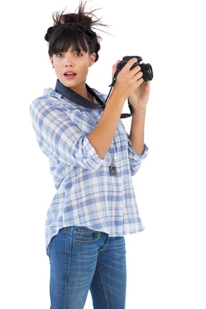 Astonished young woman taking picture with her camera on white background photo