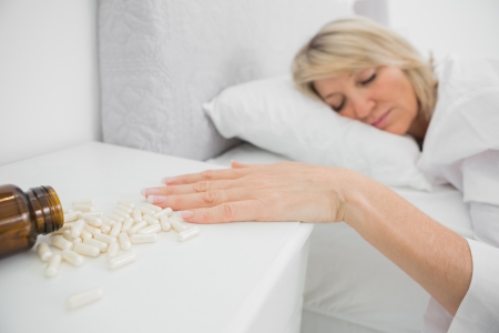 knocked over: Woman lying motionless beside pills at home in her bed