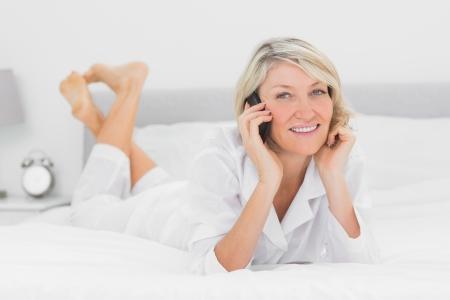 mujeres maduras: Mujer feliz que hace una llamada de teléfono acostado en la cama en su casa en el dormitorio Foto de archivo