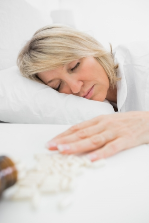 knocked over: Blonde woman lying motionless after overdose of pills at home in bed Stock Photo