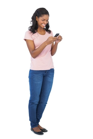 Young woman smiling and using mobile phone on white background photo