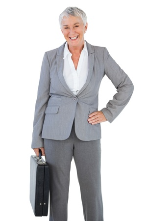 Happy businesswoman holding briefcase and putting her hand on hip on white background photo