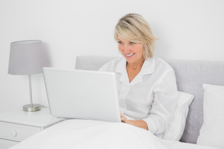 Happy woman sitting in bed with laptop at home in bedroom photo
