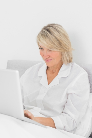 Content woman sitting in bed with laptop at home in bedroom photo