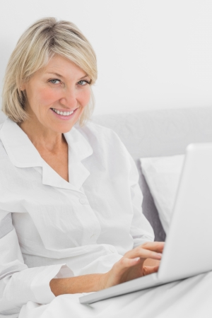 Cheerful woman sitting in bed with laptop looking at camera at home in her bedroom photo