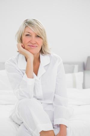 legs crossed: Cheerful  woman sitting in her bedroom looking at camera