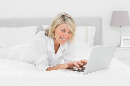 Smiling woman using her laptop on her bed looking at camera at home in bedroom photo