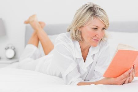 mujer leyendo libro: Mujer alegre que lee un libro que miente en cama en su casa en el dormitorio