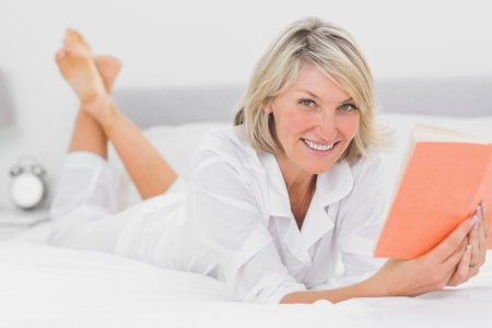Happy woman reading a book lying on bed at home in bedroom photo