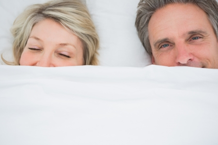 Couple waking up under the covers at home in bed photo