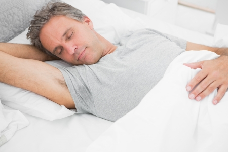 peacefully: Man sleeping peacefully at home in his bed
