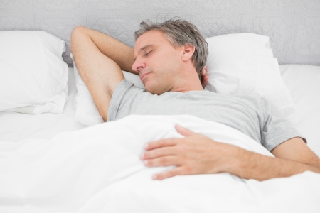 sleeping man: Man sleeping soundly in his bed at home
