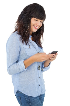 Cheerful brunette with her mobile phone texting a message on white background photo