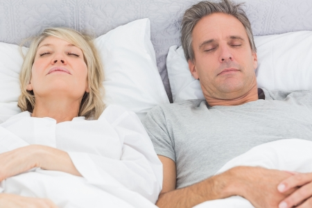 Couple sleeping in their bed at home in bedroom photo