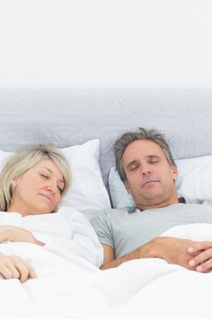 Couple sleeping soundly in their bed at home in bedroom photo