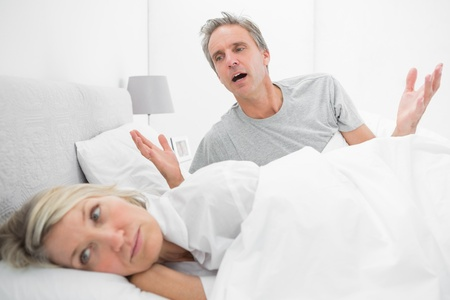 couple arguing: Man pleading with his upset partner in bed at home in bedroom