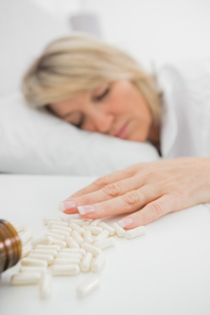 knocked over: Woman lying motionless after overdose of pills in bed at home Stock Photo