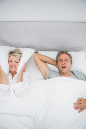 wincing: Woman blocking her ears because of partners snoring at home in bed