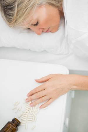 Blonde woman lying motionless after overdosing on tablets in her bed at home Stock Photo - 20626727