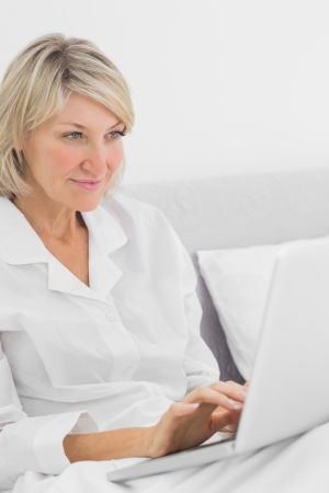 Cheerful woman sitting in bed with laptop at home in bedroom photo