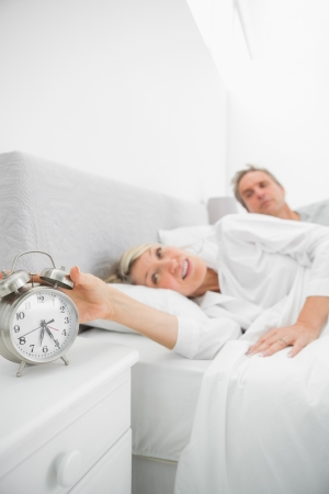 Blonde woman in bed with partner turning off alarm clock at home in bedroom photo
