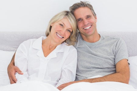 Happy couple in bed smiling at camera photo