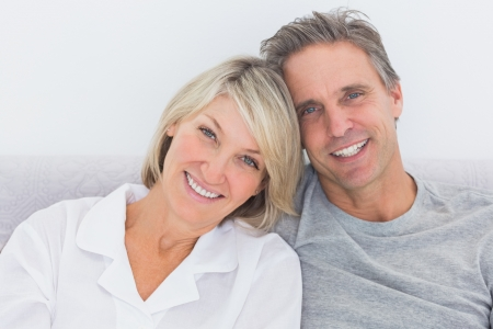 Cheerful couple in bed smiling at camera Stock Photo