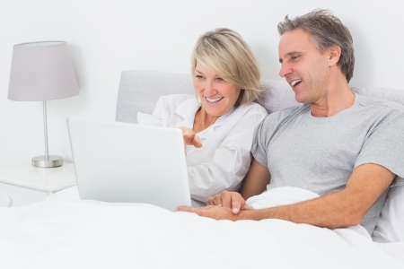 Happy couple using laptop in bed together at home photo