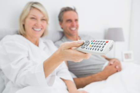 Smiling couple watching tv in bed at home in bedroom photo