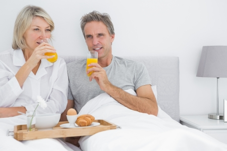 Couple drinking orange juice having breakfast in bed at home in bedroom photo