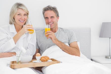 Couple drinking orange juice at breakfast in bed smiling at the camera photo
